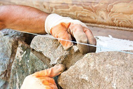 Gloved hands constructing a stone wall
