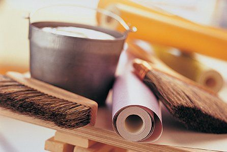 Two rolls of wallpaper, two brushes and a bucket of wallpaper paste on a wooden table