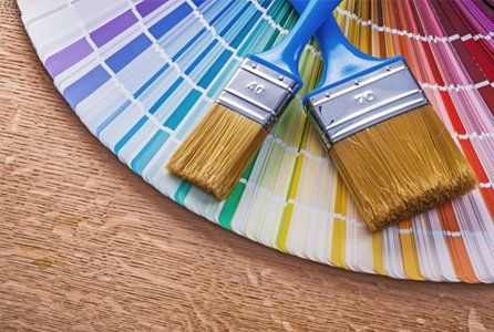 Two paint brushes on a colour sample wheel
