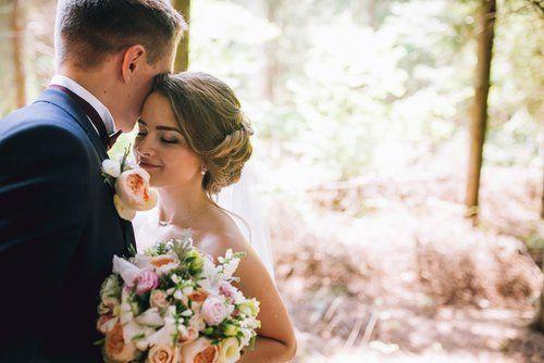 sposa e sposo in un parco con mazzo di fiori