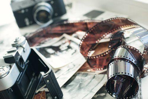 due vecchie macchine fotografiche su un tavolo con varie fotografie
