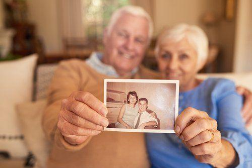 coppia anziani mentre tiene una fotografica di loro da giovani