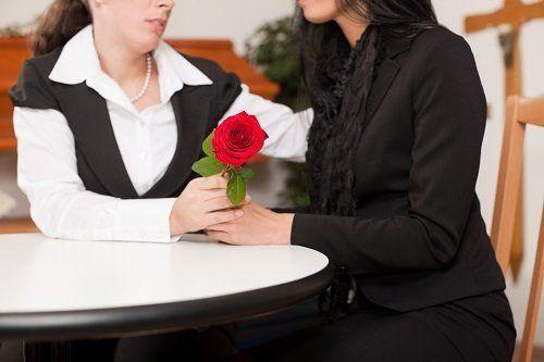 Una donna dando una rosa rossa a un'altra donna