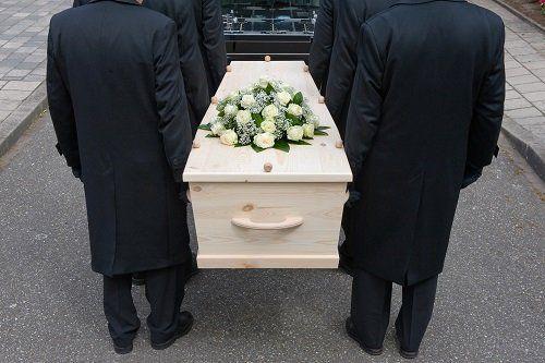dei uomini portando la bara al carro funebre