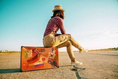 donna seduta su una valigia in una strada