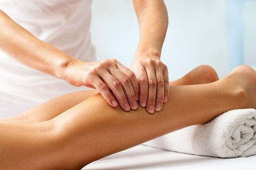 Mani che massaggiano il polpaccio d'una giovane