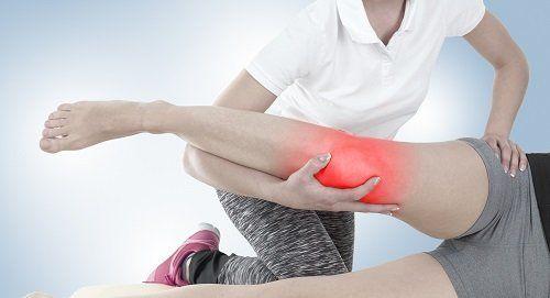Terapeuta lavorando la zona del ginocchio segnata in rosso