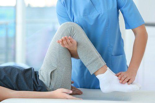 Terapeuta esercitando  le ginocchie del paziente