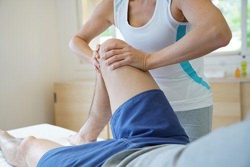 Terapeuta premendo il ginocchio destro del paziente