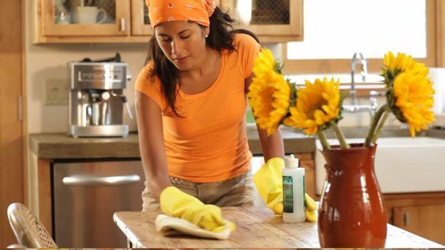 mani di una donna con guanti mentre pulisce un tavolo