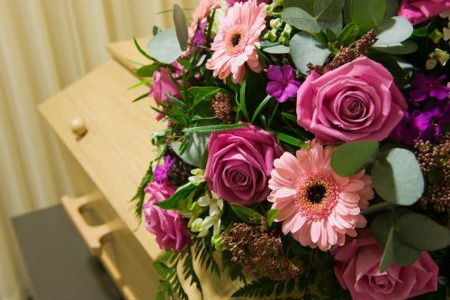 Corona di fiori in toni rose su una bara in legno chiaro