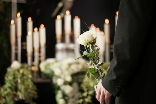 Un uomo portando una rosa bianca , dietro si vedono candele e un ataud sfuocati