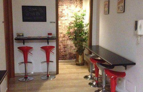 entrata con tavoli mensola a muro di color nero, 4 sgabelli di color rosso, 2 di metallo, una lavagna affissa al muro e fuori, un vaso con una pianta