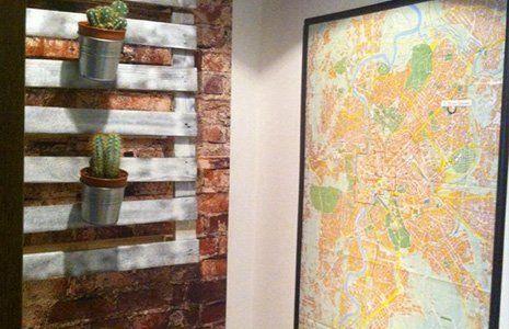 stanza con un mobile con mensole di legno fatto di mattoni a vista con dei vasi di cactus appesi e sulla sinistra una mappa in una cornice