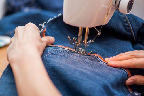 due mani che con un macchina da cucire cuciono  dei jeans