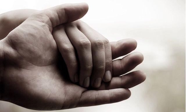 mani che si stringono nel dolore