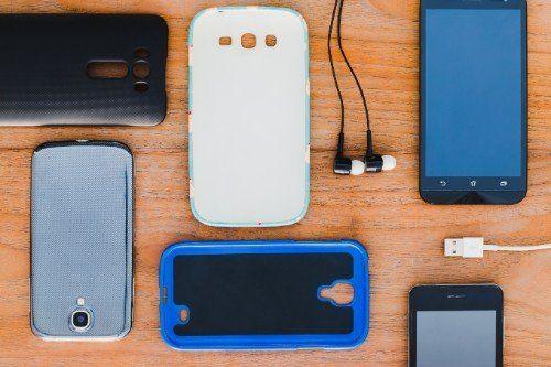 sul tavolo ci sono due cover per smartpone, delle cuffie un cavo per caricare e due smartphone
