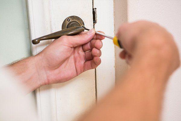 L'uomo che fissa la maniglia della porta con un cacciavite