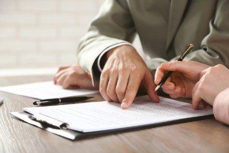 una mano che indica un documento e un'altra con una penna in mano