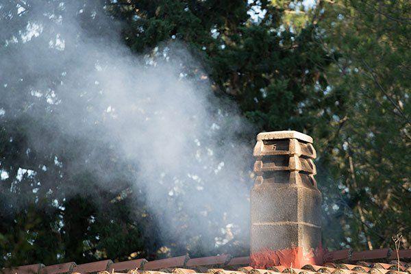 Fumo che esce da un vecchio camino di mattoni