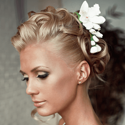 A bride with blonde hair in a curly updo, adorned with a white flower