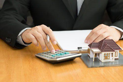 un uomo alla scrivania, con una mano usa una calcolatrice e accanto c'è un rilievo di scrittura e un modellino di una casa