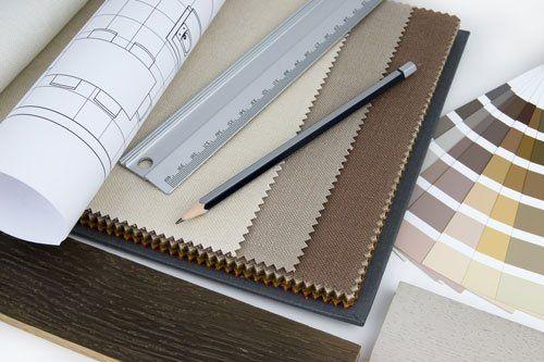 un quaderno marrone, accanto un foglio di un progetto arrotolato, un righello e una matita