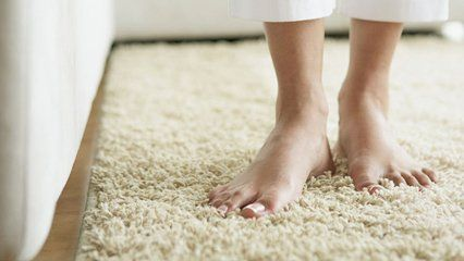 A woman stood on a thick cream coloured rug