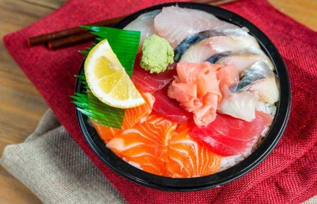 un piatto di riso e carpaccio di pesce misto