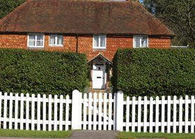 A customers house with a perfectly trimmed hedge