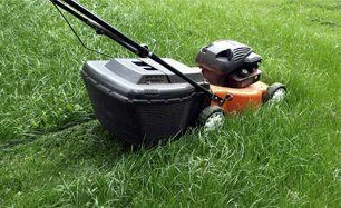 A lawn mower mowing grass