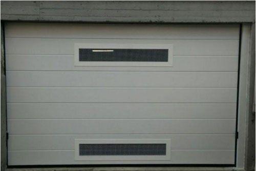 una porta di un garage di color bianco con due griglie, una sopra e una sotto