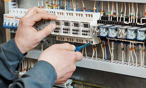 Mani di elettricista a lavoro su una centralina elettrica