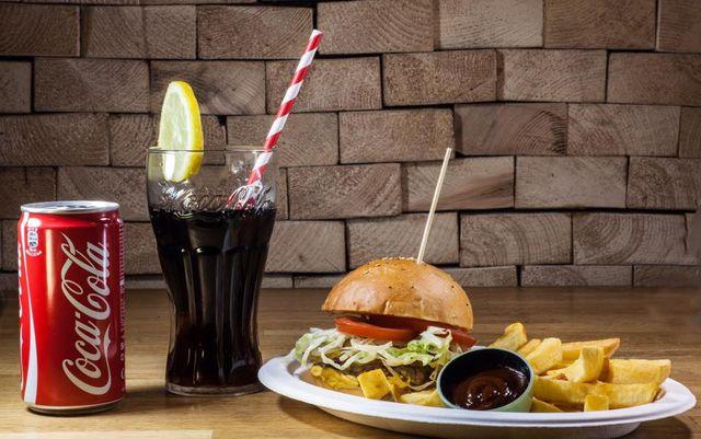 un piatto di burger con patatine fritte e una bibita Coca Cola