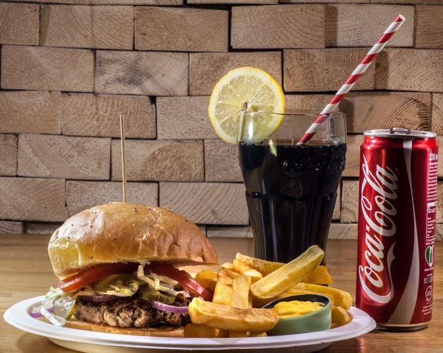 un piatto di burger con patatine fritte e una bibita