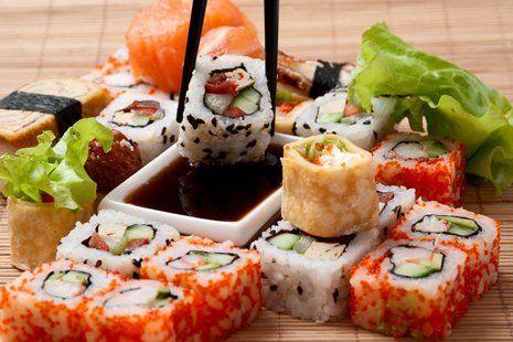 composizione di maki sushi intorno a piccolo recipiente con salsa di soia