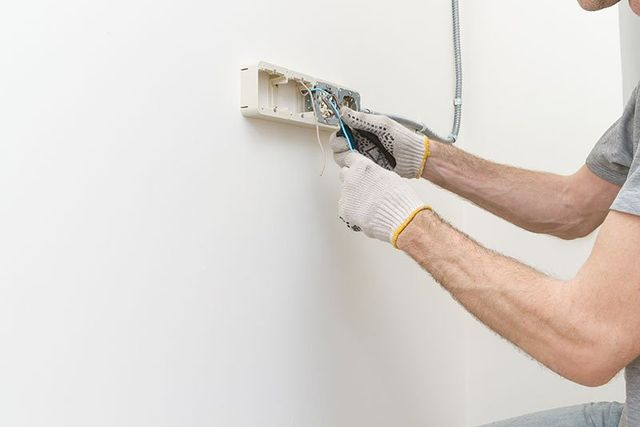 Hands professional during mounting of electrical outlets
