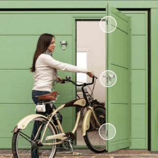 una donna con una bici che entra in una porta verde