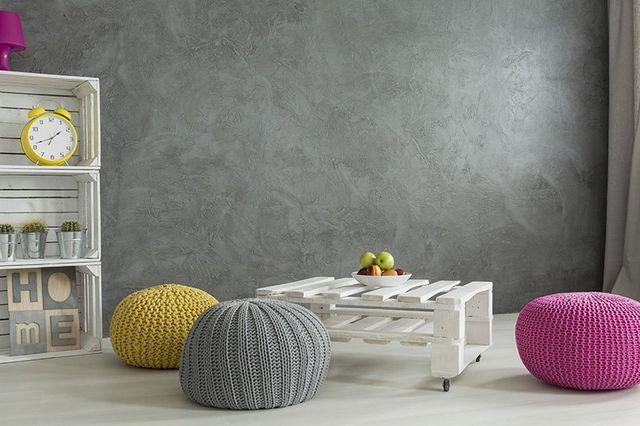 Puff rivestiti in lana di color giallo, grigio e rosa appoggiati sul parquet. Pedane e cassette in legno dipinte di bianco