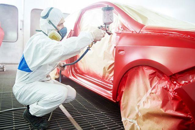 Impiegato in tuta mentre vernicia di rosso una macchina con una pistola a Illasi, VR