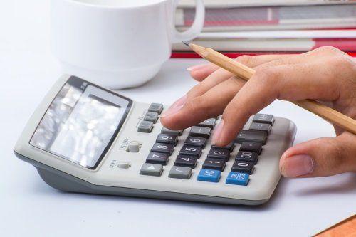 mano con matita tra le dita che digita su  una calcolatrice