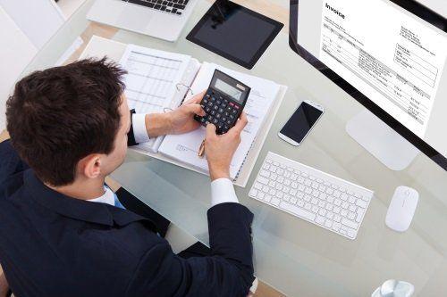 Uomo usa una calcolatrice di fronte al computer