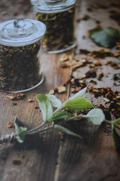 menta e due vasetti di erbe essiccate su tavolo in legno