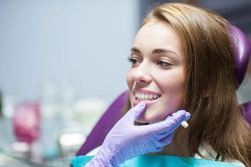 immagine di una ragazza con capelli castani seduta sulla poltrona dal dentista e una mano con un guanto in lattice azzurro che le controlla i denti