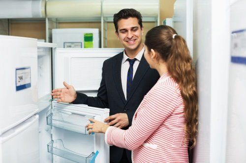 un uomo che mostra un frigorifero a una donna