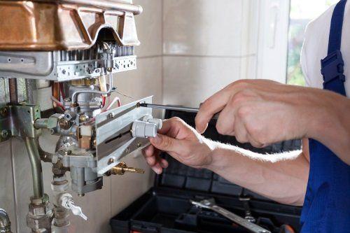 due mani con un cacciavite che sistemano una caldaia disassemblata