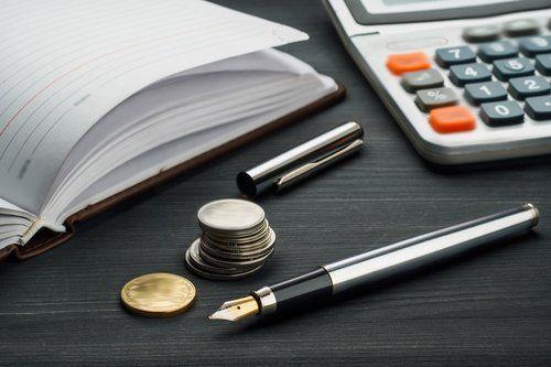 Tavolo con sopra un diario aperto, calcolatrice, monete e penna