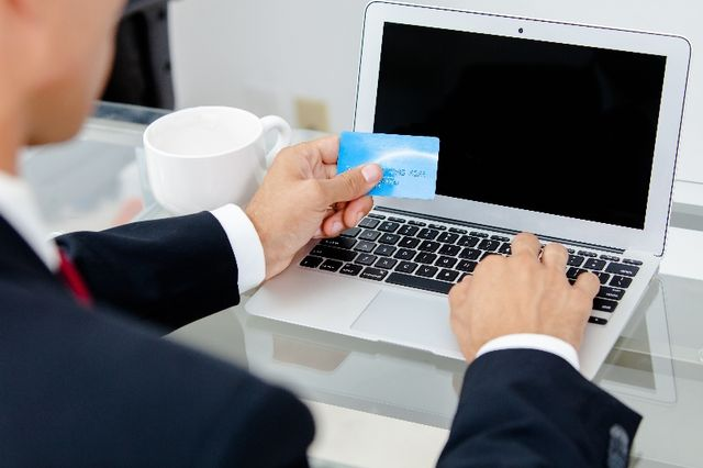 man paying bills online with card in hand