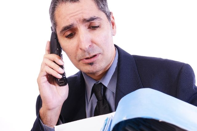 accountant working on bookkeeping and talking on the phone
