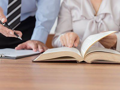 una donna che indica un libro aperto e accanto un uomo